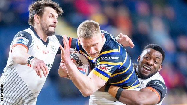 Leeds' Mikolaj Oledzki is tackled by Toronto's Jon Wilkin and Gadwin Springer