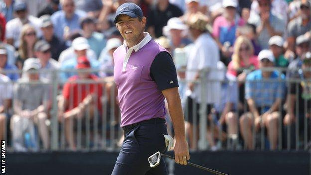 Rory McIlroy smiles with fans behind him