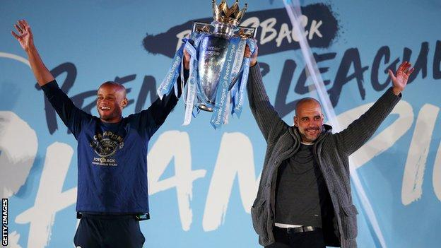 Kompany and Pep Guardiola lift the Premier League trophy aloft outside Etihad Stadium