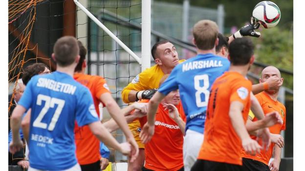Carrick Rangers keeper Brian Neeson manages to get his fingers on the ball to clear the danger against Glenavon