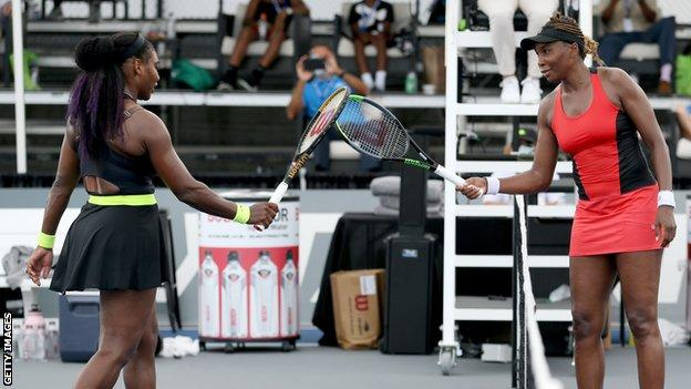 Serena Williams (left) touches racquets with sister Venus (right) after their last-16 tie at the Top Seed Open in Kentucky