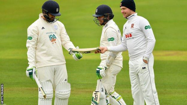 Sam Cook of Essex (right) hands Hampshire's Rilee Rossouw (left) part of his broken bat