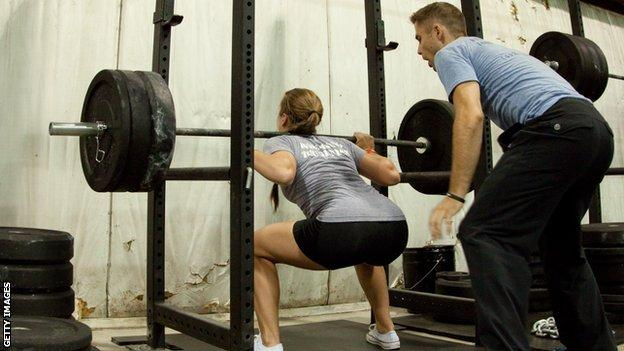 Woman being coached weightlifting