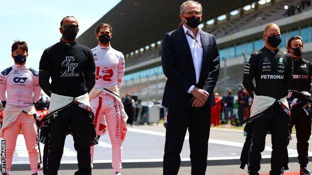 Stefano Domenicali stand next to Lewis Hamilton