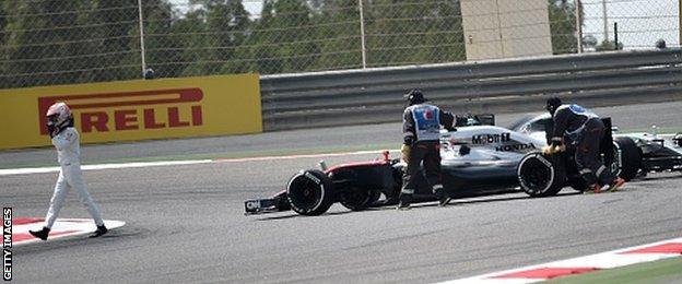 Jenson Button walking off track after a breakdown in practice