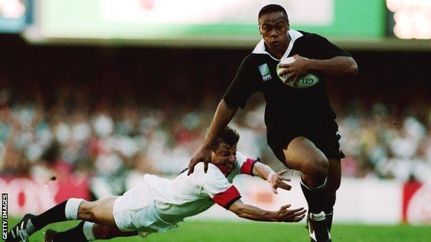Jonah Lomu evades Rob Andrew's tackle in England's defeat by New Zealand