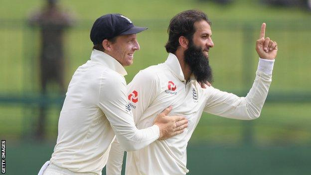 England's Jos Buttler celebrates with Moeen Ali after Moeen took a wicket on day five of the second Test against Sri Lanka