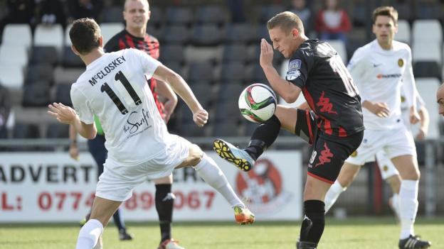 Conor McCloskey vies for possession with Matthew Snoddy as Crusaders thump Carrick Rangers 5-0 at Seaview