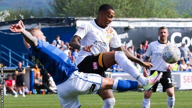 Keanu Marsh-Brown of Newport County and Elliott Durrell of Macclesfield Town compete for the ball