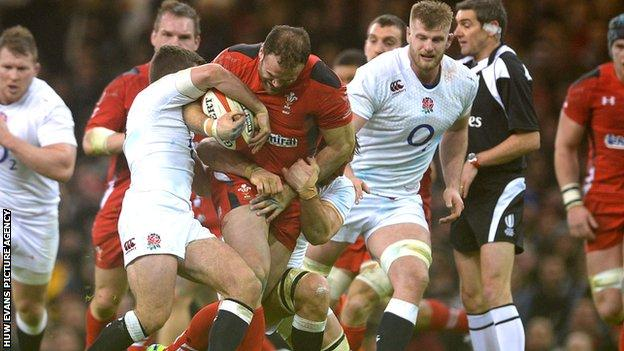 Jamie Roberts of Wales is tackled by George Ford and Ben Youngs