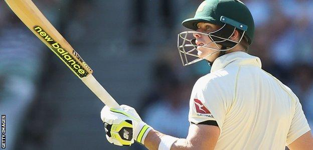 Steve Smith raises his bat after passing 50