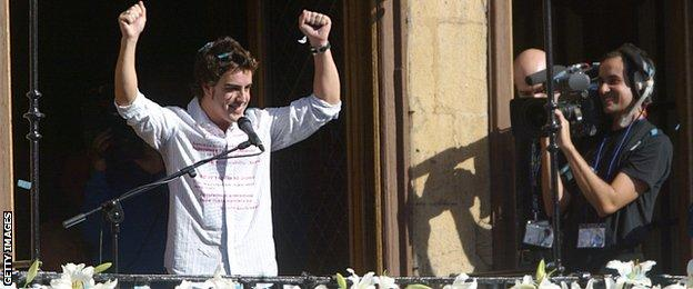 Spanish Formula 1 driver Fernando Alonso waves at supporters 29 October 2006 as they celebrate his title of world champion after his victory in the season-ending Brazilian Grand Prix at the Town Hall of his hometown, Oviedo, in northern of Spain
