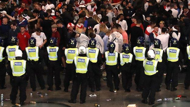 Police standing in front of England fans at Wembley