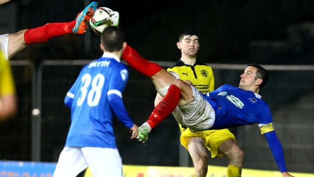 An aerial battle for the ball as Linfield striker Andrew Waterworth stretches high to challenge a Cliftonville opponent at Windsor Park