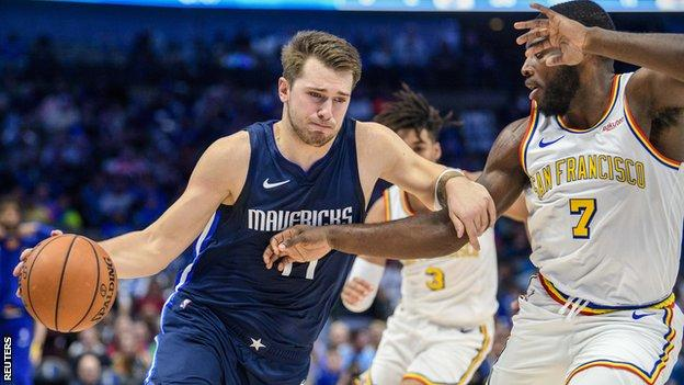 The Dallas Mavericks forward Luka Doncic (77) drives to the basket past the Golden State Warriors forward Eric Paschall (7).