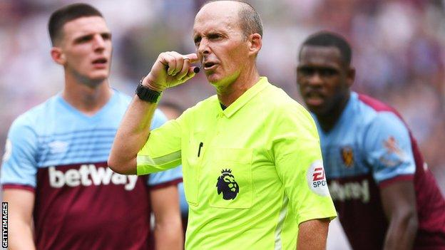 Referee Mike Dean listens for a VAR decision before awarding Manchester City a penalty during the Premier League match between West Ham United and Manchester City