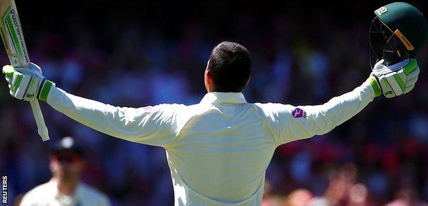 Usman Khawaja raises his bat after reaching his century at his home ground