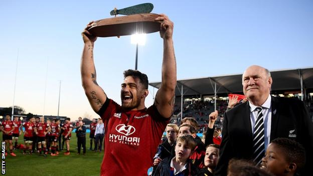 Crusaders captain Codie Taylor lifts the Super Rugby Aotearoa trophy