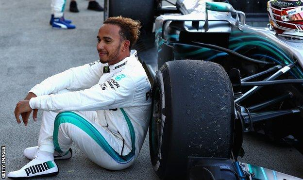 Lewis Hamilton sits by his car after the race