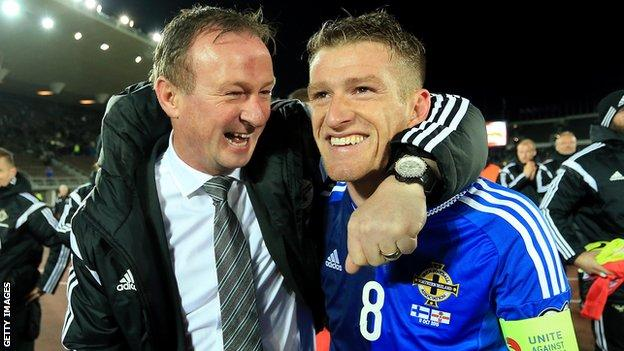 Michael O'Neill celebrates with Steven Davies