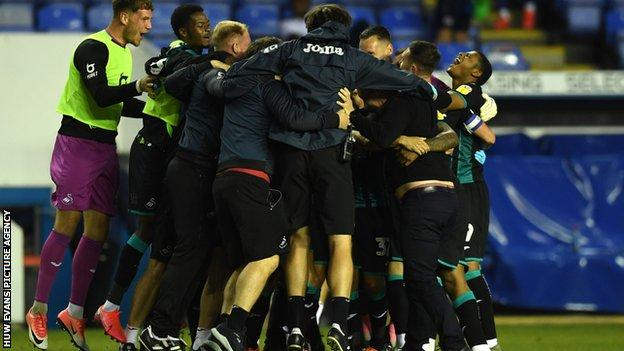 Swansea players and staff celebrate after claiming a play-off place in remarkable fashion