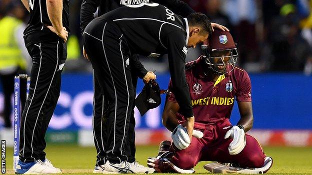 New Zealand's Ross Taylor (left) consoles West Indies' Carlos Brathwaite (right) after victory in the World Cup at Old Trafford