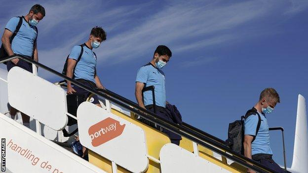 Manchester City's players get off a plane in Portugal on Monday