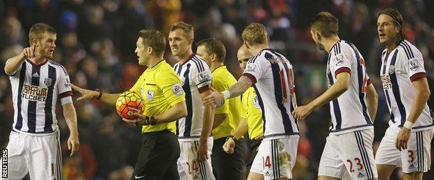 West Brom players remonstrate with referee Craig Pawson at half time