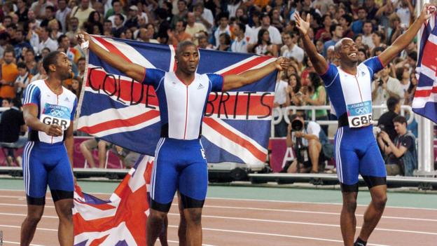 Britain's men's 4x100m team members Mark Lewis-Francis (C), Darren Campbell (L), and Marlon Devonish celebrate their gold in August 2004 at the Athens Olympics