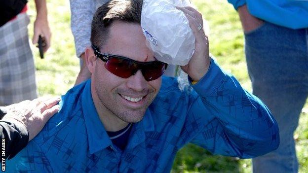 A fan holds an ice pack on his head after being hit by a stray Danny Willett drive