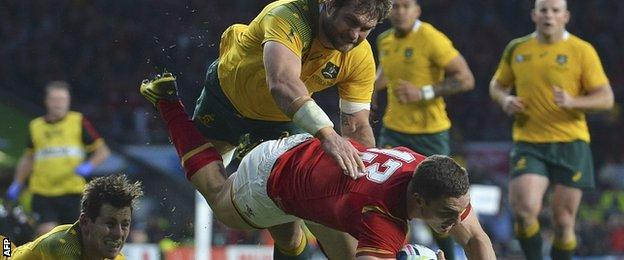 Bernard Foley (bottom left) and Ben McCalman complete a double tackle to stop Wales wing George North scoring