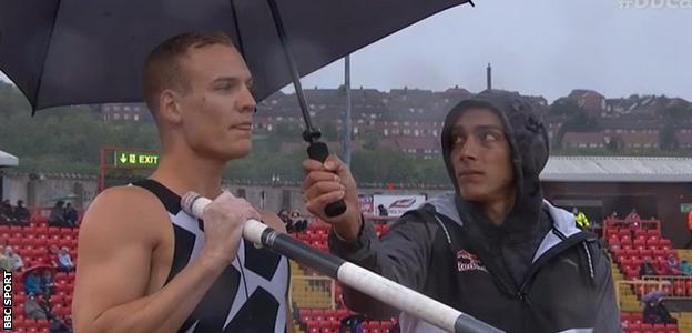 Mondo Duplantis holds an umbrella for Sam Kendricks