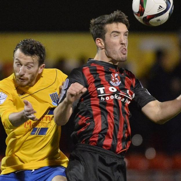 Ballymena United's Willie Faulkner loses out in an aerial battle with Crusaders defender Josh Robinson at Seaview
