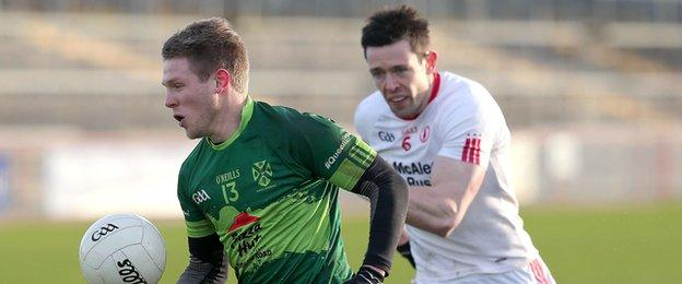 Michael Monan of Queen's and Tyrone's Conor Clarke contest for possession at Healy Park