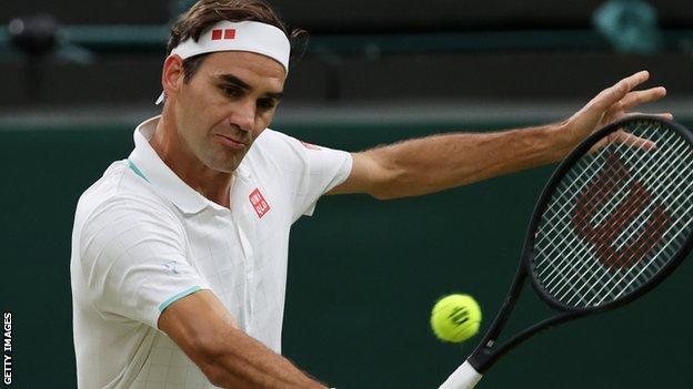 Roger Federer returns in his match against Lorenzo Sonego