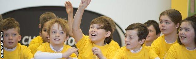 Children raise their hands to ask James Taylor questions during a Chance to Shine event
