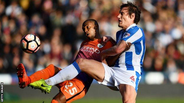 Man City's Fernandinho and Huddersfield's Dean Whitehead challenge for the ball