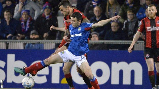Crues midfielder Declan Caddell and Linfield's Stephen Fallon tussle for the ball