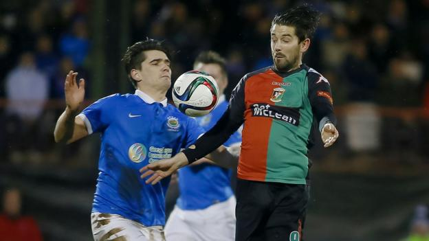 Linfield defender Jimmy Callacher battles for the ball with Curtis Allen of Glentoran during the Belfast derby clash at the Oval