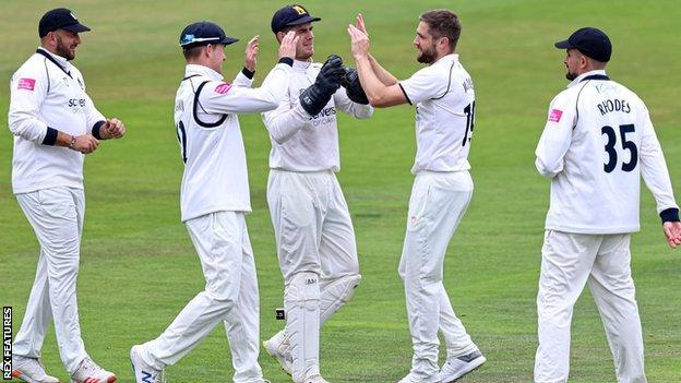 Warwickshire's Chris Woakes celebrates taking the wicket of England team-mate Dawid Malan at Headingley