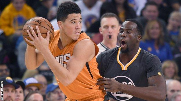 Phoenix Sun' Devin Booker (left) is guarded by Golden State Warriors' Draymond Green during an NBA game