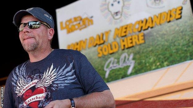 John Daly sells merchandise to fans on Washington Road outside his mobile home prior to the 2010 Masters Tournament at Augusta National Golf Club on April 5, 2010