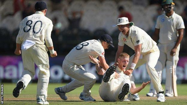 England's Ben Stokes falls to the ground and is mobbed by team-mates after taking a wicket on day five of the second Test against South Africa
