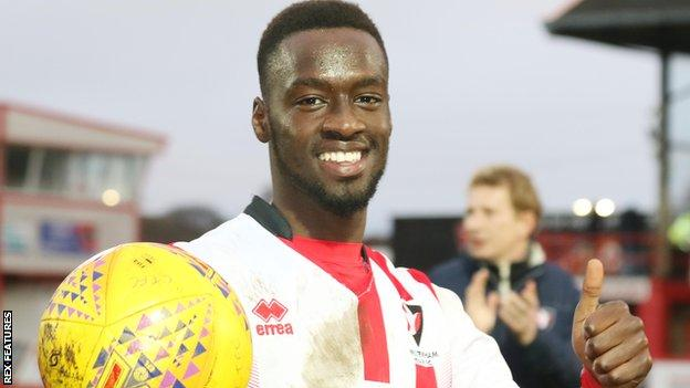 Mohamed Eisa poses with the match ball after scoring a hat-trick for Cheltenham