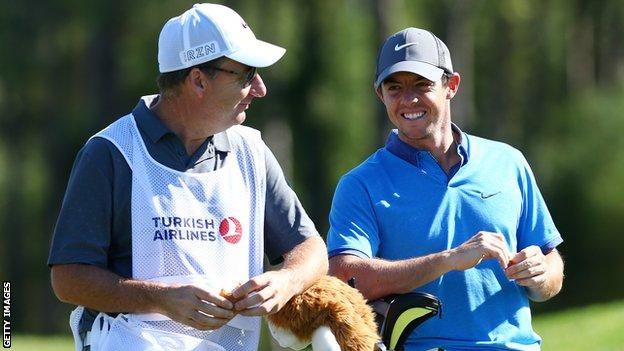 Rory McIlroy consults with his caddie during a practice round ahead of the Turkish Airlines Open