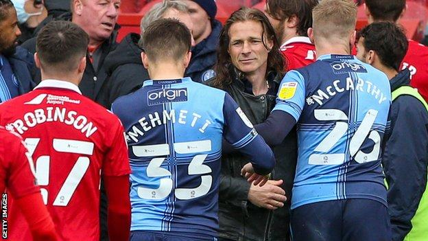 Wycombe boss Gareth Ainsworth consoles his players