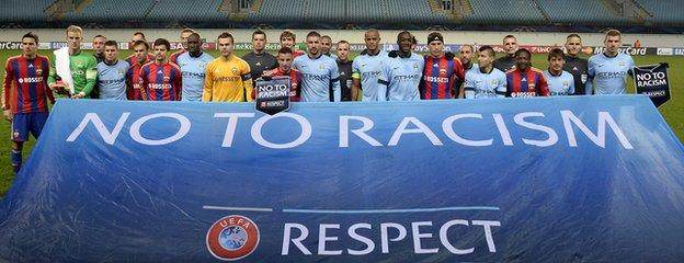 Players pose behind an anti-racism banner in the empty Khimki Arena before the UEFA Champions League group E football match between CSKA Moscow and Manchester City in Moscow on 21 October, 2014