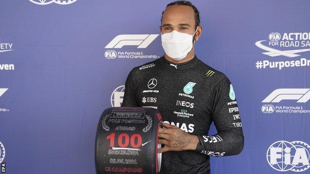 Lewis Hamilton sostiene su neumático número 100 en el sitio de lanzamiento