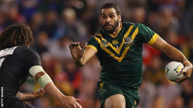 Greg Inglis fends away Kevin Proctor while playing for Australia v New Zealand
