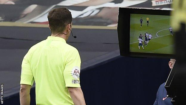 Referee Peter Bankes looks at the monitor